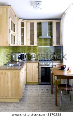 Kitchen - natural wood cabinets with glass and stone tiles - stock photo