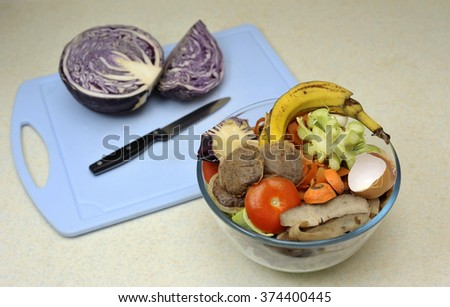 Kitchen raw food waste, beside cabbage being prepared, collected in a bowl for adding to a home composter or compost heap. - stock photo