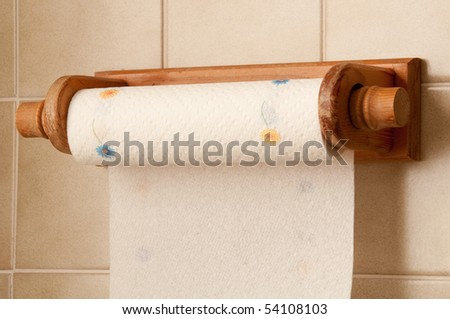 Kitchen roll holder on a tiled wall - stock photo