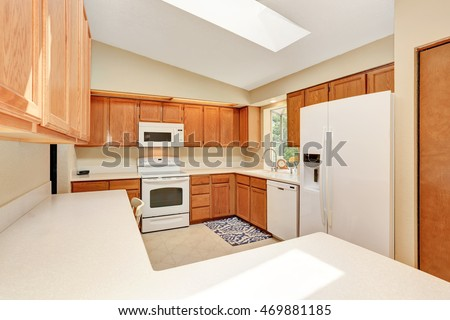 Kitchen room interior in white tones with wooden cabinets and white counter top. Northwest, USA
