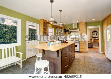 Kitchen room interior with green wall and tile floor. Furnished with large wooden kitchen island, light brown cabinets and white stools. Also with view of dining room.