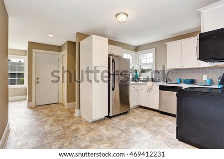 Kitchen room interior with white cabinets and tile floor. Northwest, USA