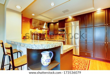 Kitchen room with black wood cabinets, marble counter tops, steel appliances and wooden bar stools - stock photo