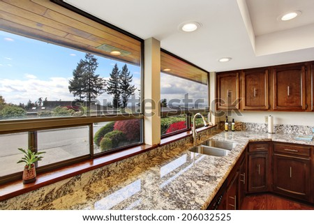 Kitchen room with dark brown cabinets and granite counter top. - stock photo