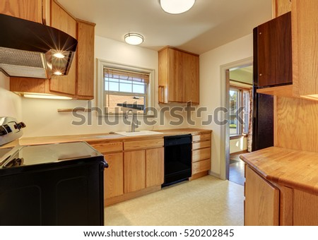 Kitchen room with flat panel cabinets and black appliances. Northwest, USA