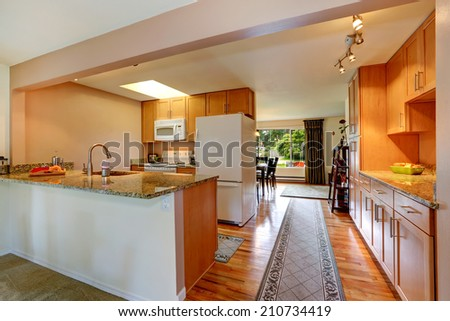 Kitchen room with white appliances and light tone cabinets. View of walk-through hallway with rug - stock photo