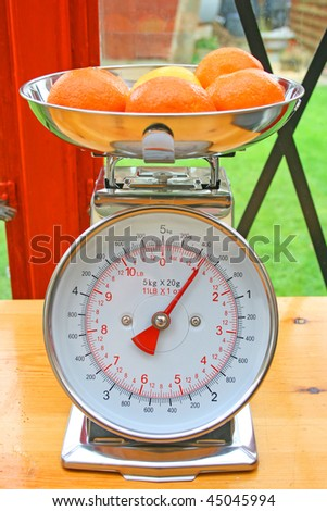 Kitchen scales and fruit. - stock photo
