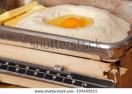Kitchen scales with egg butter and flour - stock photo