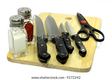 Kitchen set. Different sizes kitchen knifes, scissors, salt and pepper shakers over wooden cutting board.