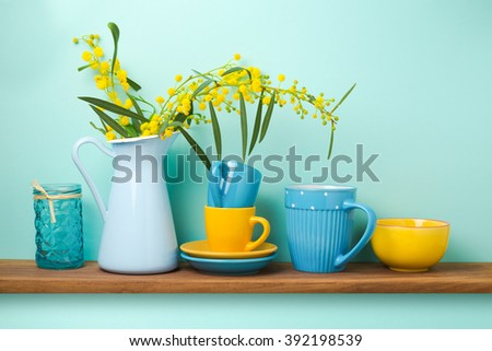 Kitchen shelf with flowers in vase and tableware - stock photo