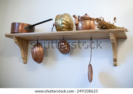kitchen shelf with old copper utensils on white wall background - stock photo