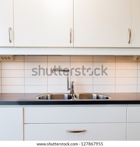 kitchen sink and white cupboards - stock photo