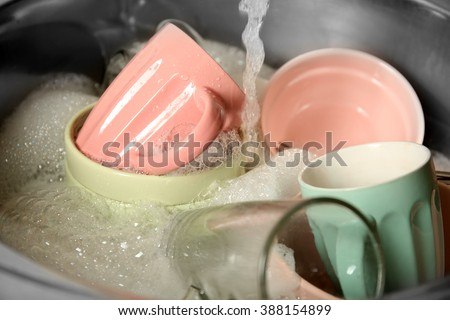 Kitchen sink full of dishes closeup - stock photo