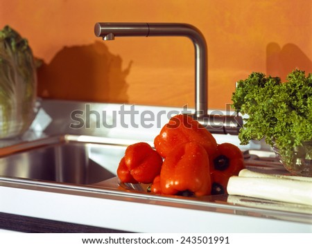 kitchen sink macro photo of vegetables and herbs in the foreground small deep of field - stock photo