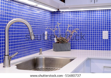 Kitchen sink, white counter with chrome faucet and blue tile walls - stock photo