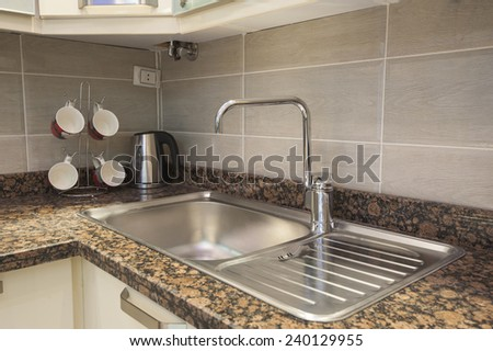 Kitchen sink with tap on marble counter and kettle next to mug tree in apartment - stock photo