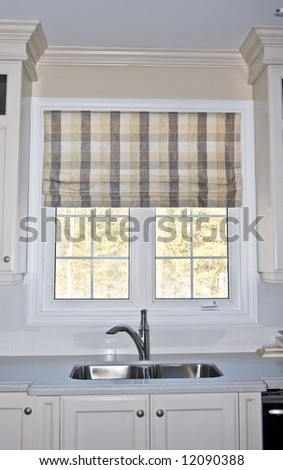 Kitchen sink with window looking outside.  Roman shade is the window covering.