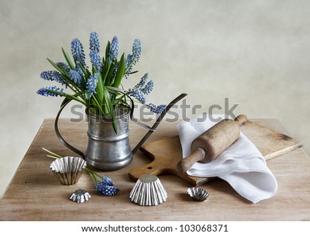 Kitchen still life with grape hyacinths in an old pewter watering can surrounded by retro cooking utensils on a rustic wooden table