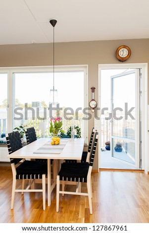 kitchen table by the window and open door to the balcony - stock photo