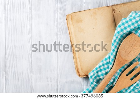 Kitchen table with blank vintage recipe cooking book and utensils. Top view with copy space - stock photo