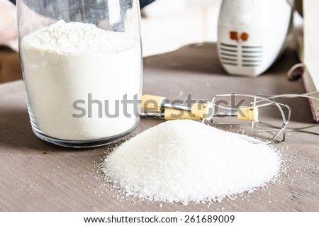 Kitchen table with flour in cup and white sugar on the table with beaters and cooking book on background.