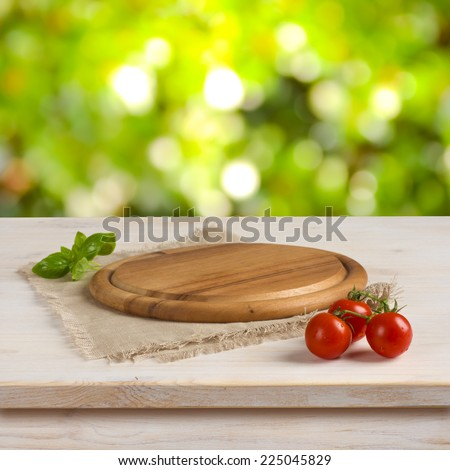 Kitchen table with round board over green bokeh background - stock photo