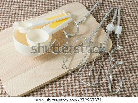 Kitchen Tools and Equipment, Four Plastic Measuring Spoons in Different Sizes with Metal Whisk on Wooden Cutting Board. - stock photo