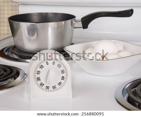 Kitchen tools for boiling eggs on stove - stock photo