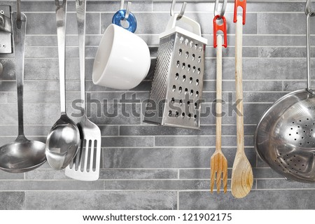 Kitchen tools on a grey tile marble wall - stock photo