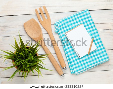 Kitchen utensil and notepad over white wooden table background. View from above with copy space - stock photo