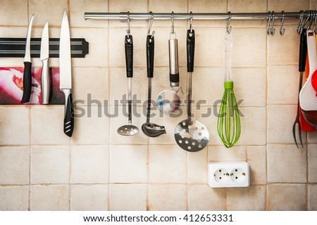 Kitchen utensils, a brown tiled wall background