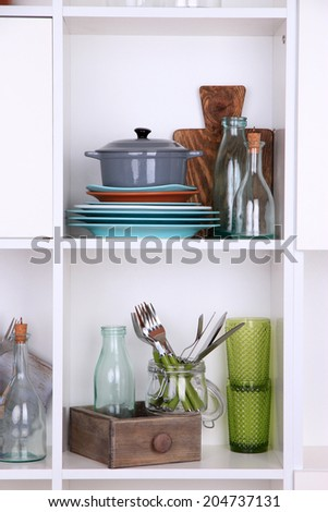 Kitchen utensils and tableware on beautiful white shelves - stock photo
