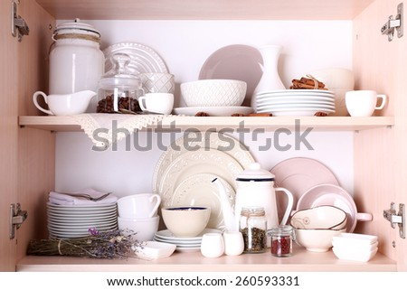 Kitchen utensils and tableware on shelves - stock photo