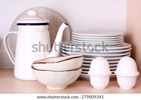 Kitchen utensils and tableware on wooden shelf - stock photo