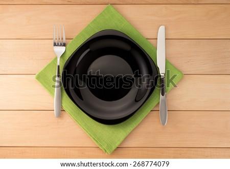 kitchen utensils at cloth napkin on wooden background - stock photo
