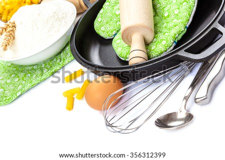 Kitchen utensils, eggs, flour for baking and frying pan isolated on white background. - stock photo