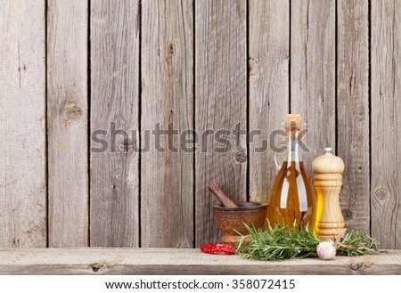 Kitchen utensils, herbs and spices on shelf against rustic wooden wall - stock photo