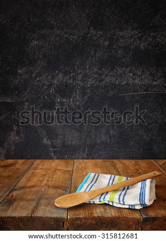 Kitchen utensils on tablecloth on wooden textures table against chalkboard background  - stock photo