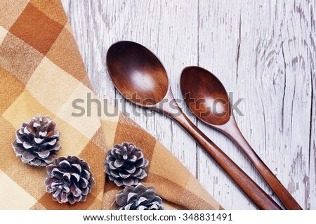 Kitchen utensils over white wooden table background. Two wooden spoons and brown cloth in a section on an old wooden textural surface. View from above with copy space.  - stock photo
