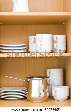 Kitchen-ware in top closet on wooden shelves. - stock photo