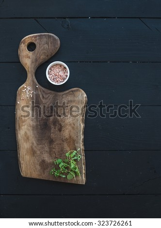 Kitchen-ware set. Old rustic chopping board made of walnut wood, salt and oregano herb on a black background, top view, copy space - stock photo