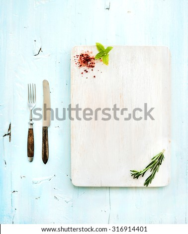Kitchen-ware set. White wooden chopping board, knife, fork, spices and herbs on a light blue background, top view - stock photo