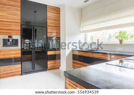 Kitchen with black marble worktop and fridge