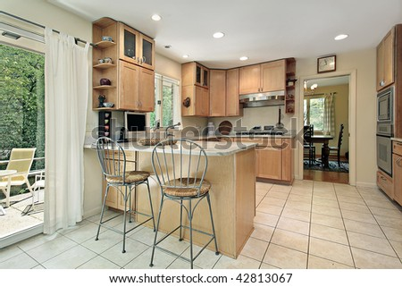 Kitchen with breakfast bar and patio view - stock photo