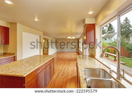 Kitchen with bright wooden cabinets and granite tops. Kitchen room has kitchen island. Empty living room