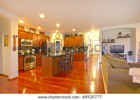 Kitchen with dark golden cherry cabinets and matching hardwood floor.. - stock photo