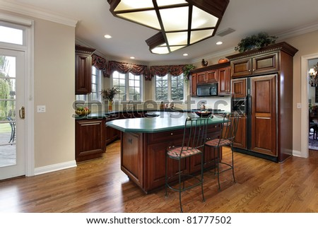 Kitchen with dark wood cabinets and green island counter - stock photo