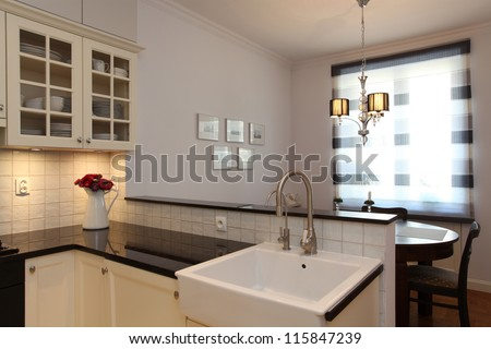 Kitchen with farmhouse sink and round table - stock photo