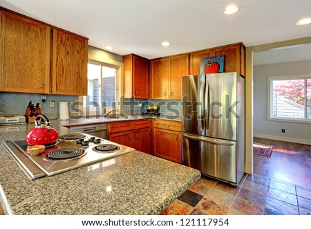 Kitchen with granite counter top stove and red tea pot.