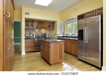 Kitchen with granite top island and yellow walls - stock photo